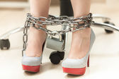 Photo of women legs in high heeled shoes locked by chain — Stock Photo