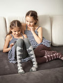 Two sisters using tablet on couch — Stock Photo