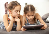 Concentrated young girls using digital tablet — Stock Photo