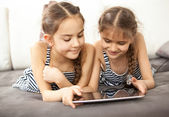 Smiling schoolgirls lying on couch and playing on tablet — Stock Photo