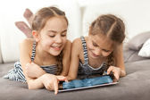 Portrait of two smiling girls lying on couch and using tablet — Stok fotoğraf