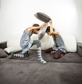 Girls fighting with cushions on couch — Stock Photo