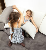 Girls having pillow fight on bed — Stock Photo