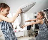 Portrait of two little sisters fighting with pillows — Stock Photo