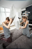 Young sisters pillow fighting on couch — Stock Photo