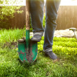 Man holding foot on shovel at garden at sunny day — Stock Photo #46566309