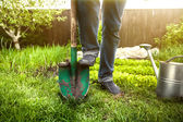 Man holding foot on shovel at garden at sunny day — Stock Photo