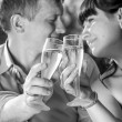 Monochrome portrait of just married couple drinking champagne — Stock Photo