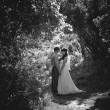 Monochrome photo of bride and groom kissing under high trees — Stock Photo #46821179