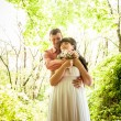 Portrait of groom hugging bride under tree at park — Stock Photo