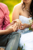 Groom putting golden ring in brides hand at park — Stock Photo