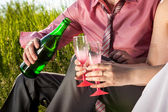 Photo of groom pouring champagne at brides glass at meadow — Stock Photo
