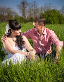 Groom hugging bride on big field at sunny day — Stock Photo