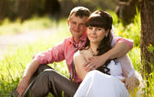 Portrait of happy groom hugging bride under tree at sunny day — Stock Photo