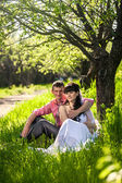Newly married couple hugging under tree at alley — Stock Photo