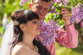 Groom giving lilac flowers on branch to bride — Stock Photo