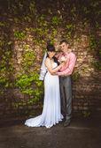 Evli çift eski tuğla duvara sarılma — Stok fotoğraf