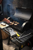 Man cooking marbled meat on barbecue for burgers — Stock Photo