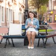 Woman with tablet relaxing on bench after shopping  — Photo #50037355