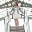 Woman standing on top of escalator at shopping mall — Stock Photo #50039963