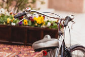 Toned photo of retro bicycle against violet flowerbed — Stock Photo