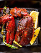 Cooked lobster claw with lemon and vegetables — Stock Photo