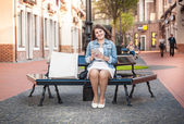Woman with tablet relaxing on bench after shopping  — Stock Photo