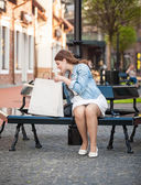 Woman looking inside of white shopping paper bag on bench — Stock Photo