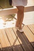 Slim legs in ballet flats on wooden bridge at summer day — Stock Photo