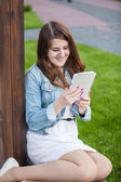 Brunette student reading book on tablet at park on grass — Stock Photo