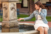 Beautiful woman holding hand under fountain — Stock Photo