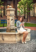 Beautiful woman reading book on tablet on side of fountain — Stock Photo