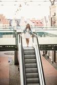 Woman walking down the escalator at shopping mall — Stock Photo