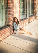 Woman sitting on street and leaning against brick wall — Stock Photo