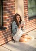 Young woman sitting on street and using tablet — Stock Photo