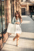 Happy woman with white paper bag at shopping mall — Stock fotografie