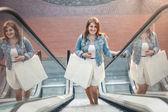 Shopping woman in shopping mall on escalator — Stock Photo