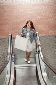 Woman with paper bag going on escalator at shopping mall — Stock Photo