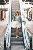Woman walk on escalator holding white paper bag — Stock Photo