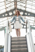 Woman standing on top of escalator at shopping mall — Stock Photo