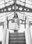 Monochrome shot of woman descend the escalator  — Stock Photo