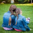 Little sisters sitting on grass head to head with joint braids — Stock Photo #50041305