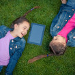 Little girls lying face to face on grass and looking at tablet — Stock Photo #50041433