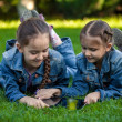 Two small sisters with tablet lying on grass at park — Stock Photo #50041743