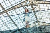 Woman talking on cellphone at airport with glass ceiling — Stock Photo