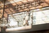 Young woman walking with shopping bag at terminal — Stock Photo