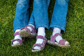 Similar legs in sandals of twin girls — Stock Photo