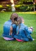 Little sisters sitting on grass head to head with joint braids — Стоковое фото