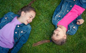 Two little girls lying on grass face to face and laughing — Stock Photo
