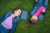 Little girls lying face to face on grass and looking at tablet — Stock Photo